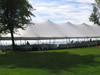 Tent with White Plastic Chairs At Lake